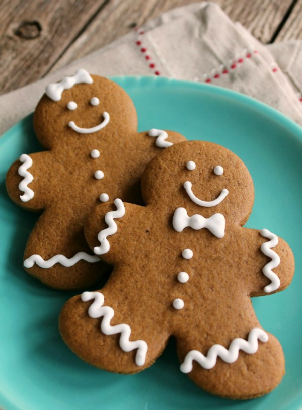 Two smiling frosted gingerbread cookies stacked on a green plate
