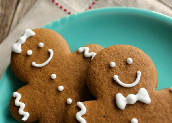 Two smiling gingerbread cookies on a green plate